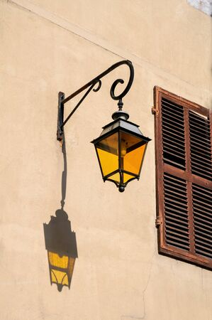 Photo pour Retro yellow lantern is projected on the wall with shuttered window, Annecy, France - image libre de droit