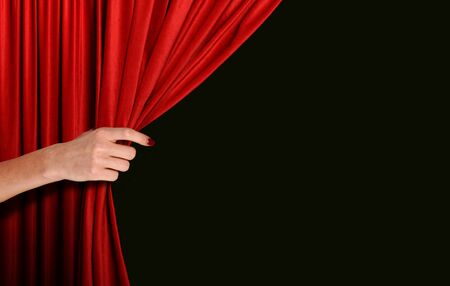 Photo pour Hand opening red curtain over black background - image libre de droit