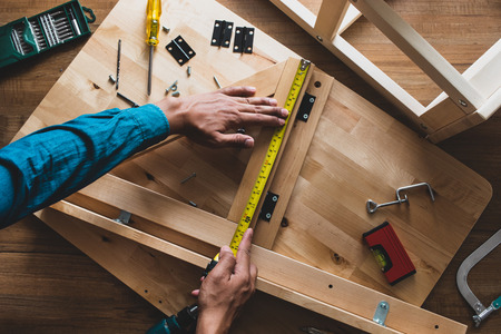 Photo pour Man assembly wooden furniture,fixing or repairing house with yellow tape measures.top view - image libre de droit
