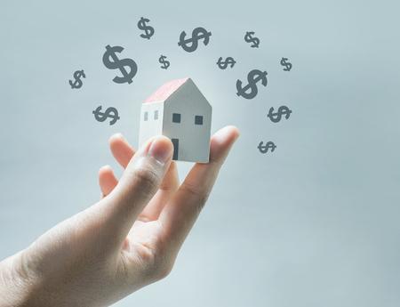 Foto de House model on human hands with dollar icon.Savings money and real estate concept - Imagen libre de derechos