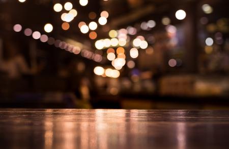 Foto de Wood table top with reflect on blur of lighting in night cafe,restaurant background/selective focus. - Imagen libre de derechos