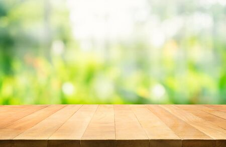 Foto de Empty of wood table top on blur of fresh green abstract background .For montage product display or design key visual layout - Imagen libre de derechos