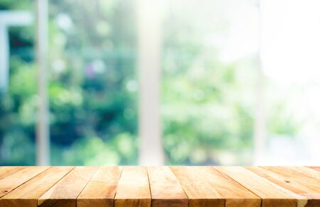 Photo pour Wood table top on blur of window with garden flower background in morning.For montage product display or design key visual layout - image libre de droit