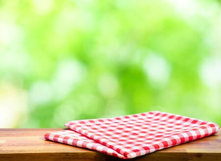 Foto für Red checked tablecloth on wood with blur green bokeh of tree background.Summer and picnic concepts.Design for key visual food and drink products.no people - Lizenzfreies Bild