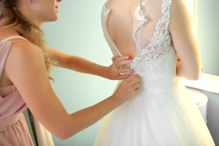 Foto de Bridesmaid helping slender bride lacing her wedding white dress, buttoning on delicate lace pattern with fluffy skirt on waist. Morning bridal preparation details newlyweds. Wedding day moments, wear. - Imagen libre de derechos