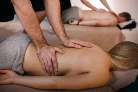 Foto de A man and a woman relax in the spa salon, professional massage therapists do a massage, the guy and the girl enjoy - Imagen libre de derechos