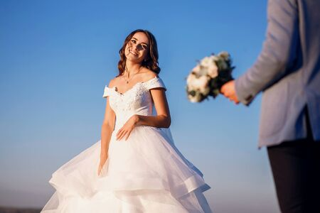 Photo pour The bride and groom are standing near the river against the blue sky - image libre de droit