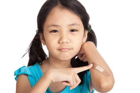 Little asian girl point to bandage on her arm  isolated on white background
