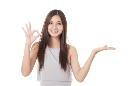 Beautiful young Asian woman show palm hand and OK sign  isolated on white background