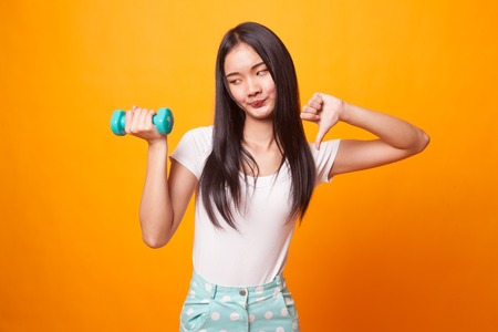 Unhappy Asian woman thumbs down with dumbbells on bright yellow background