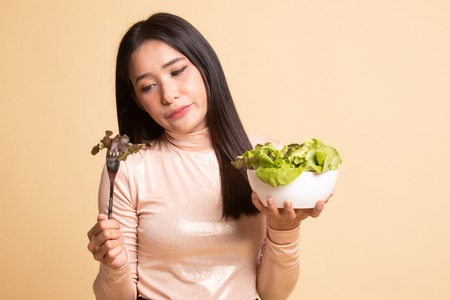 Photo pour Asian woman hate salad on  beige background - image libre de droit