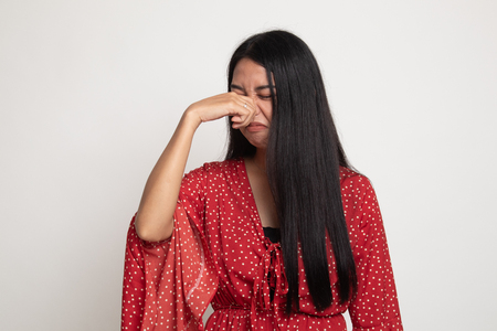 Photo for Young Asian woman  holding her nose because of a bad smell on white background - Royalty Free Image