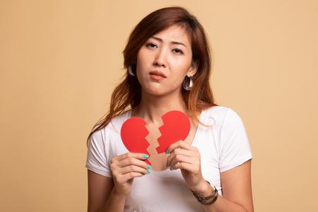 Foto de Beautiful young Asian woman with broken heart on beige background - Imagen libre de derechos