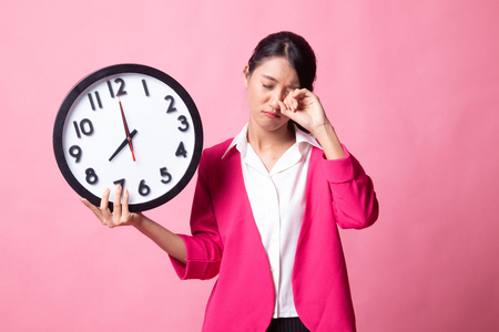 Photo for Sleepy young Asian woman with a clock in the morning on pink background - Royalty Free Image