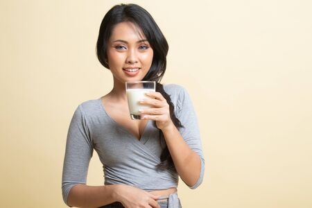 Photo for Healthy Asian woman drinking a glass of milk   on beige background - Royalty Free Image