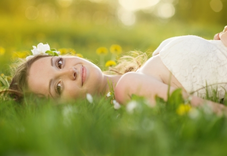 Photo pour Beautiful girl is relaxing lying on the grass in the garden - image libre de droit