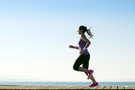 Foto de Young woman is running in sunny nature - Imagen libre de derechos