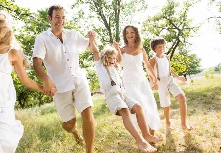Foto de Happy young family spending time outdoor on a summer day - Imagen libre de derechos