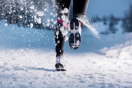 Athlete woman is running during winter training outside in cold snow weather の写真素材