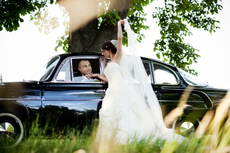 Happy bride and groom in a black car on wedding day