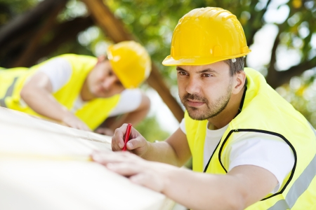 Photo for Construction workers collaborating on new house building - Royalty Free Image