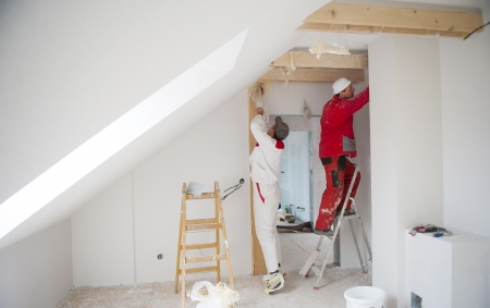 Photo pour Construction worker is painting the wall in new house - image libre de droit