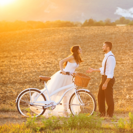 Foto de Beautiful bride and groom wedding portrait with white bike - Imagen libre de derechos