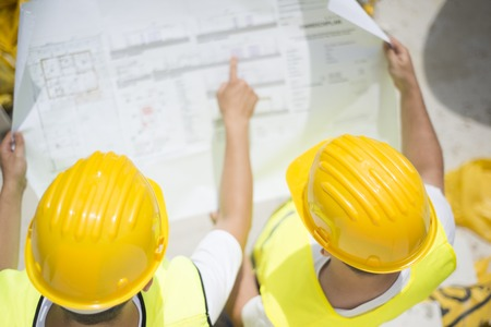 Photo for Engineer builders in safety vest with blueprint at construction site - Royalty Free Image