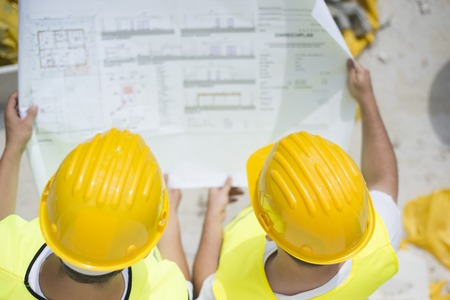 Photo pour Engineer builders in safety vest with blueprint at construction site - image libre de droit