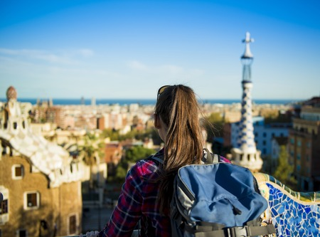 Rear view of young female tourist looking at view in Parc Guell in Barcelona, Spain