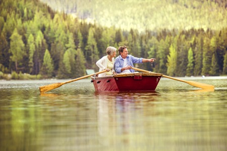 Photo pour Senior couple paddling on boat with mountains in background - image libre de droit