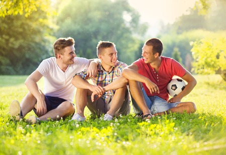 Photo for Three happy friends spending free time together in park sitting on grass and chatting - Royalty Free Image
