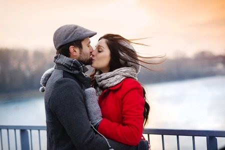 Young couple kissing by the river in winter weather