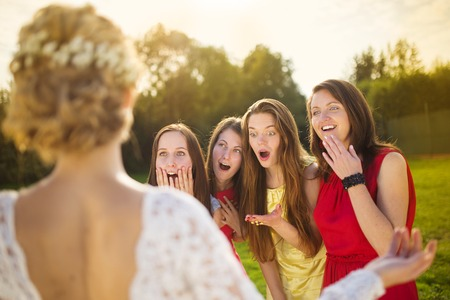 Portrait of surprised bridesmaids looking at beautiful bride outside