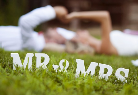 Foto de Happy bride and groom enjoying their wedding day in green nature, lying on grass - Imagen libre de derechos