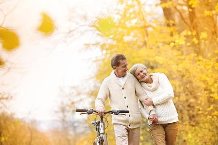 Foto de Active senior couple together enjoying romantic walk with bicycle in golden autumn park - Imagen libre de derechos