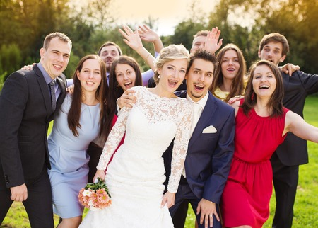 Photo pour Portrait of newlywed couple having fun with bridesmaids and groomsmen in green sunny park - image libre de droit