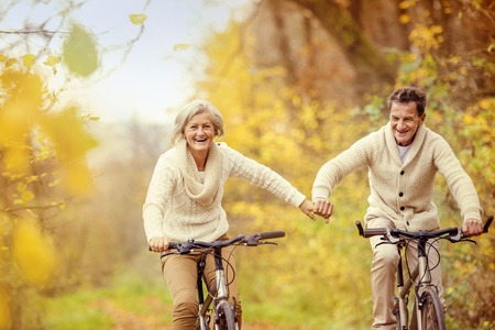 Photo for Active seniors riding bike in autumn nature. They relax outdoor. - Royalty Free Image