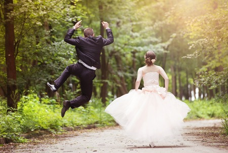 Wedding couple - bride and groom - running down the roadの写真素材