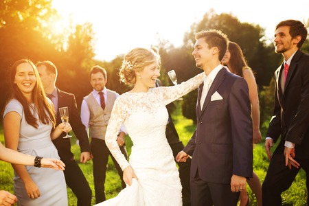 Full length portrait of newlywed couple dancing and having fun with bridesmaids and groomsmen in green sunny park