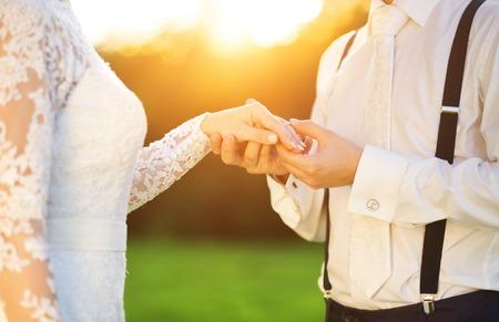 Foto de Young wedding couple holding hands as they enjoy romantic moments outside on a summer meadow - Imagen libre de derechos