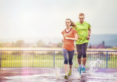 Young couple jogging on asphalt in rainy weatherの写真素材