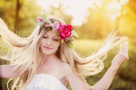 Attractive young woman with flower wreath on her head with sunset in background.の写真素材