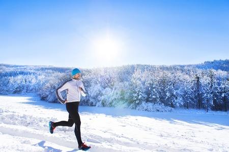 Foto de Young sportsman jogging outside in sunny winter park - Imagen libre de derechos
