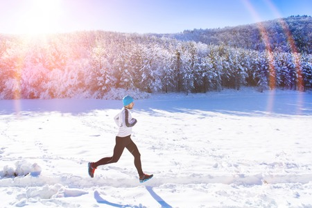 Photo pour Young sportsman jogging outside in sunny winter park - image libre de droit