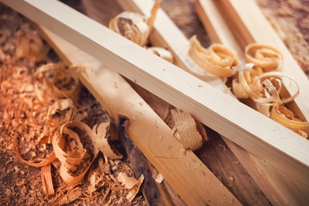 Wooden planks and shavings at carpenters workshop
