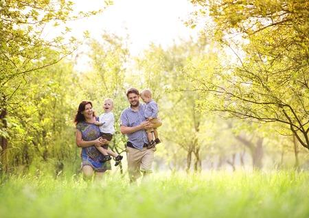 Foto de Happy young family spending time together outside in green nature. - Imagen libre de derechos