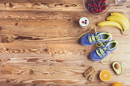 Photo pour Pair of running shoes and healthy food composition on a wooden table background - image libre de droit