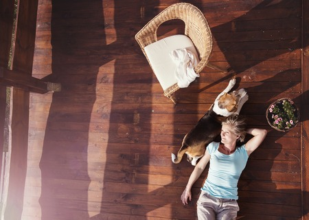 Photo pour Senior woman with her dog on a terrace of her house. - image libre de droit