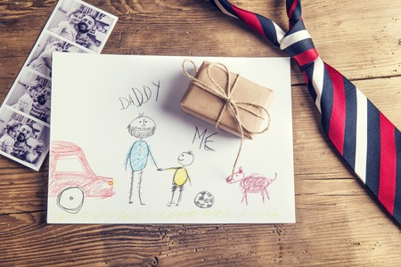 pictures of father and daughter, child\'s drawing, present and tie laid on wooden desk background.